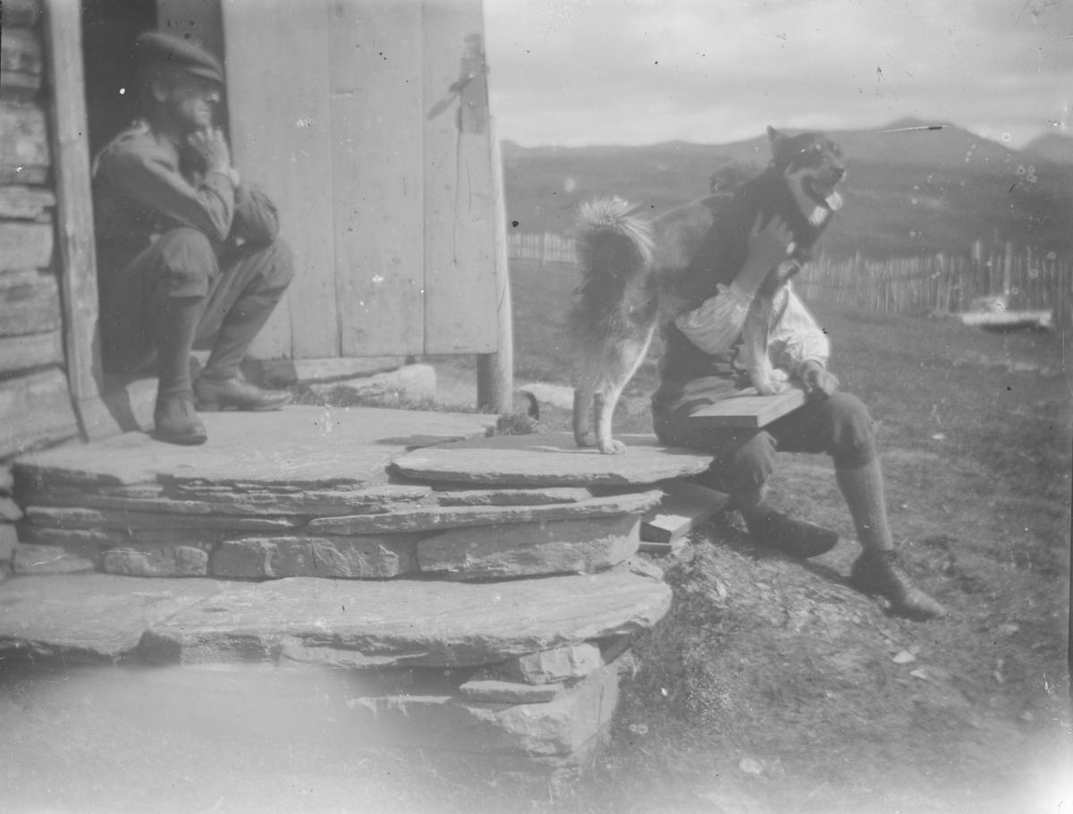 To menn og en hund sitter ved inngang med steintrapp