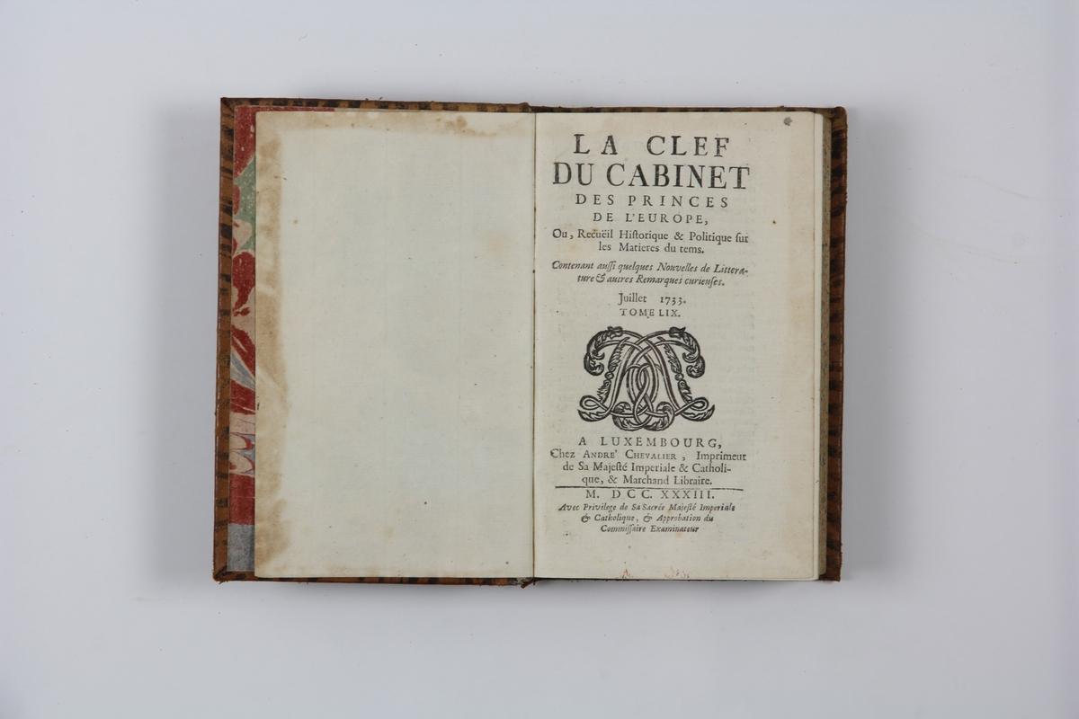 """Bok, helfranskt band """"La clef du cabinet des princes de l´Europe"""", del 59, tryckt i Luxemburg 1733. Skinnband med blindpressad och guldornerad rygg i fem upphöjda bind, titelfält med blindpressad titel,  fält med volymens nummer (nästan utplånat), fält med ägarens initialer samt påklistrad pappersetikett. Pärmens insidor klädda med marmorerat papper. Med rödstänkt snitt."""