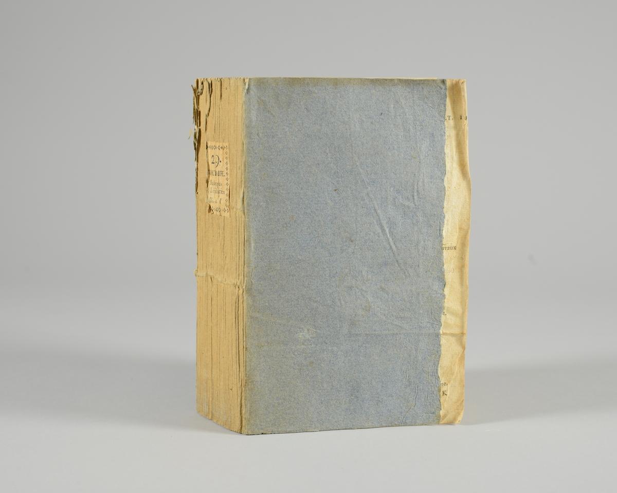 """Bok, pappband,""""Oeuvres completes de Voltaire"""", del 29, tryckt 1785. Pärmen klädd med gråblått papper, skurna snitt. På ryggen klistrad pappersetikett med tryckt text samt volymens nummer. Ryggen blekt."""