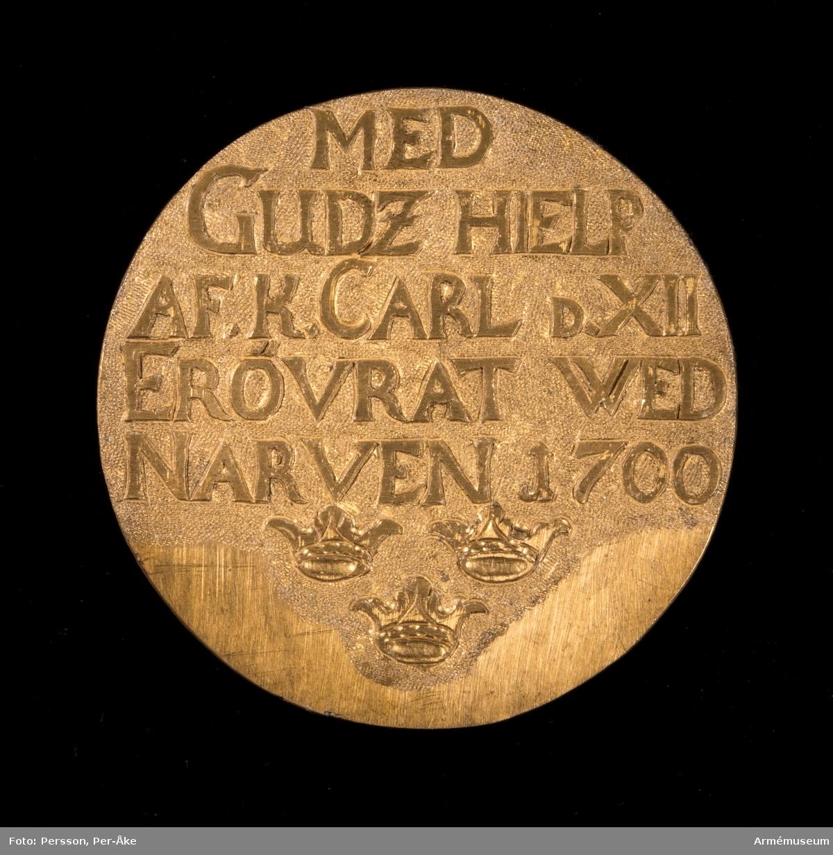 Grupp: M II.  Åtsidan: Inskription i relief: MED GUDZ HIELP AF. K. CARL D XII ERÖVRAT WED NARVEN 1700. Nedanför tre kronor -två över en.  Frånsidan: har reminisenser av tre stämplar: Tre kronor med ...ARKIVET -skall troligen vara KRIGSARKIVET.
