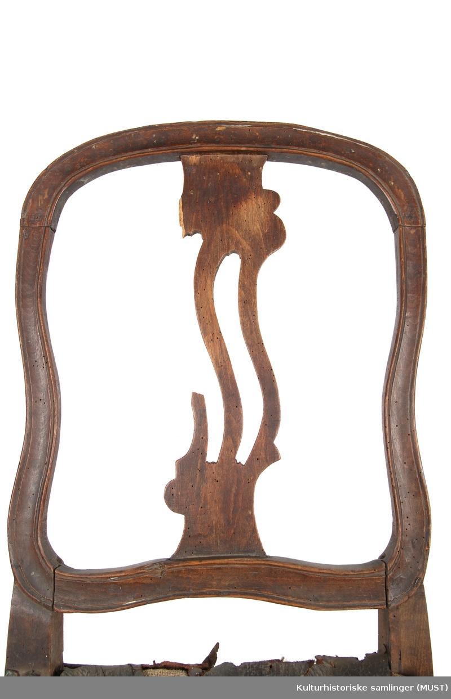 Svungne bein. Åpen rygg med gjennombrutt ryggbrett. Usymetrisk ryggbrett.  Ryggens ramme er profilert. Skinntrukket sete. Meget ramponert. stolens profilerte ramme peker mot Louis seize-stil.