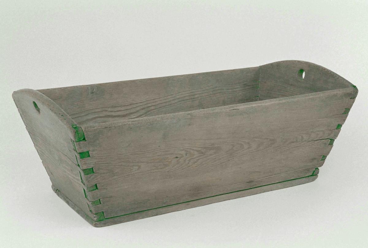 Baktråg av trä, rektangulär med sluttande sidor, laxade hörn, rundade kortsidor, runda urtag till handtag.