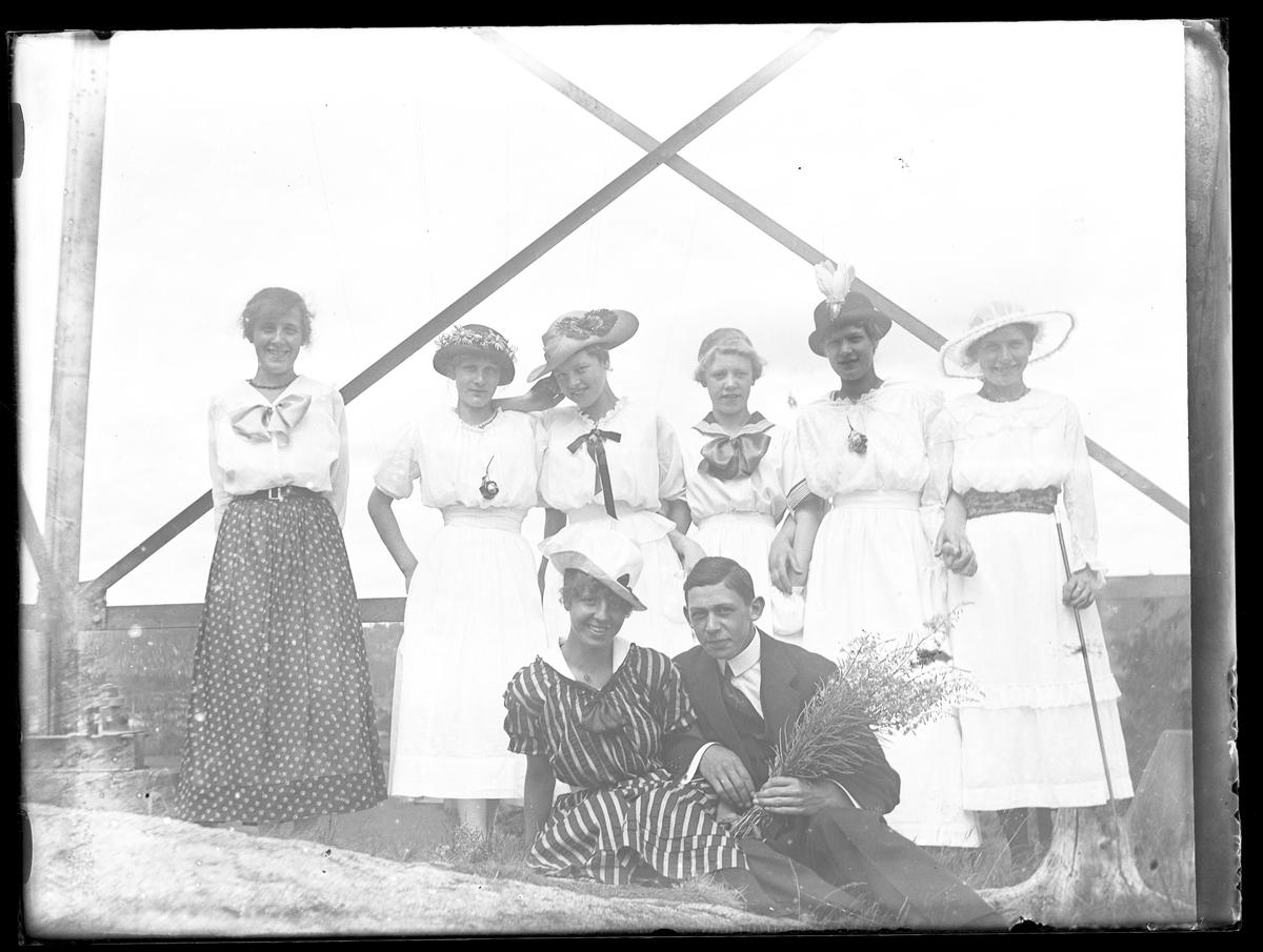 En ej namngiven flicka, Ebba, Tulli,  Signe, Greta och ej namngiven flicka står arm i arm medan Ruth och en pojke (Harald Olsson?) sitter arm i arm framför dem. Pojken håller en bukett blommor i handen.