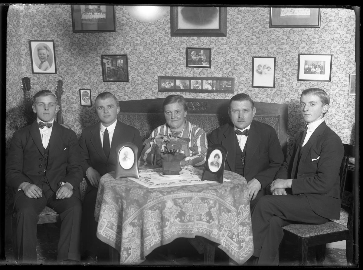 Carl Andersson med familj sitter runt ett bord i ett finrum.
