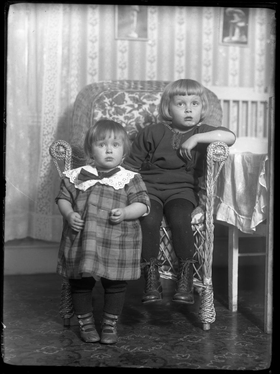 """Bengt Fredrik Nilsson sitter i en korgstol medan hans syster Gerd Anna-Lisa Nilsson står på golvet framför. I fotografens anteckningar står det """"Porträtt av Hjalmar Nilssons barn."""""""