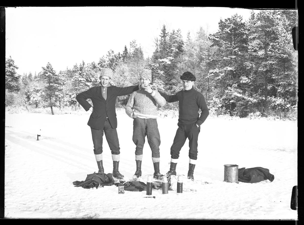 """Tre vinterklädda män håller om varandra på isen. Framför dem ligger termosar och utrustning. Mannen i ljus pälsmössa och kavaj är troligen Hugo Larsson. I fotografens egna anteckningar står det """"Angelfiske på Mörke"""". Om det är Lilla eller Stora Mörken framgår inte."""