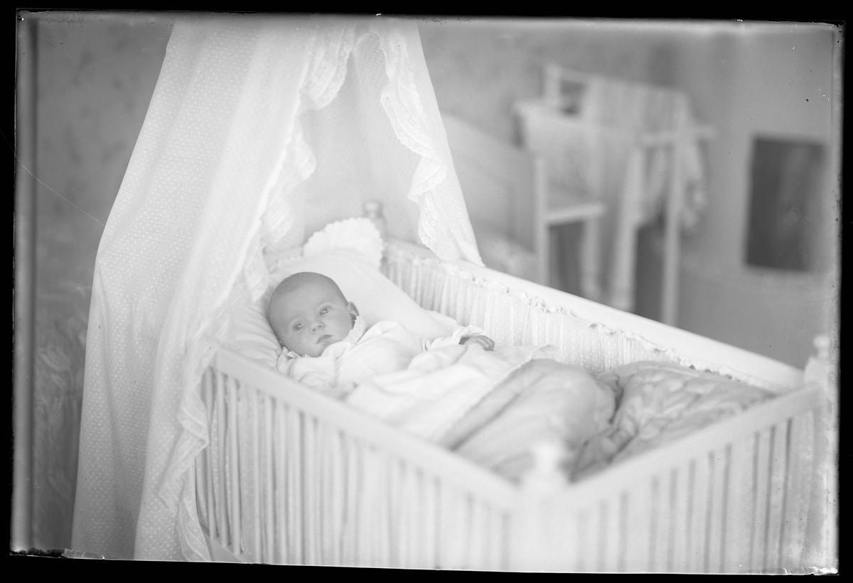 """Ett litet barn, tolkat som Elsa Margareta Berg, ligger nedbäddad i en himmelssäng. I fotografens anteckningar står det """"Ing[enjör] Bergs dotter""""."""