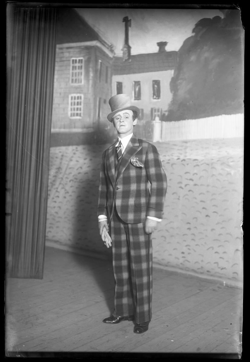 Georg Johansson,  fotograferad i samband med medverkan i nyårsrevyn, står klädd i rutig kostym och hög hatt framför en målad kuliss.