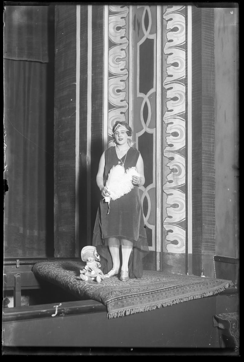 Asta Karlander, fotograferad vid Nyårsrevyn, står vid kanten av en scen. I handen har hon en vit solfjäder och vid hennes fötter sitter en docka.
