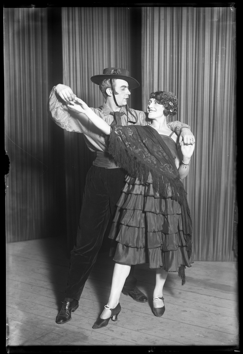 """En man och en kvinna poserar framför kameran i samband med Nyårsrevyn. I fotografens egna anteckningar står det """"Nyårsrevyn Tangoparet"""". Tolkat som att kvinnan är Dana Klinge."""