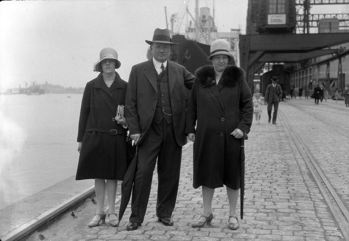 """Två kvinnor och en man står vid vattnet i en hamn, troligen Frihamnen i Göteborg. I bakgrunden syns människor, ett fartyg samt byggnader. I fotografens egna anteckningar står det """"Maggnussons, Gbg""""."""