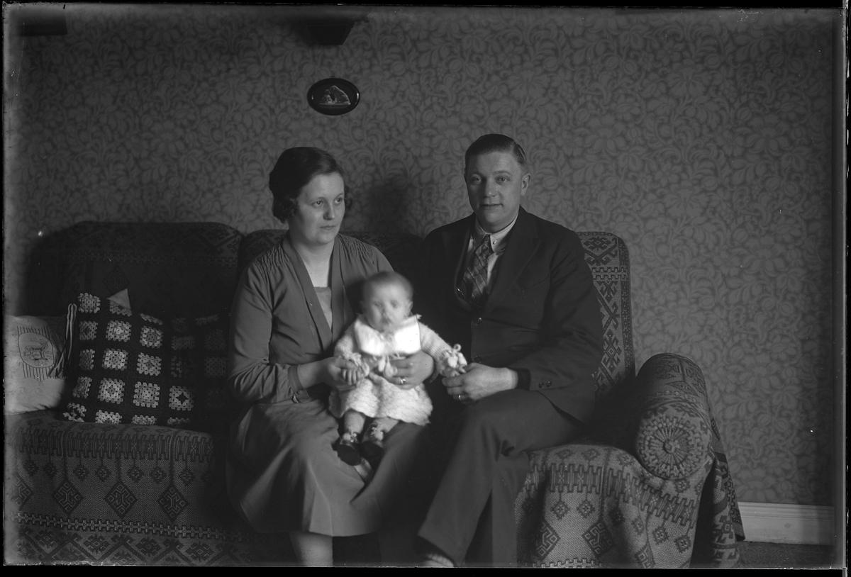 """Familjen Pettersson sitter i en soffa. Sonen sitter i sin mammas knä och håller föräldrarna i handen. I fotografens egna anteckningar står det """"Sven Pettersson med familj""""."""