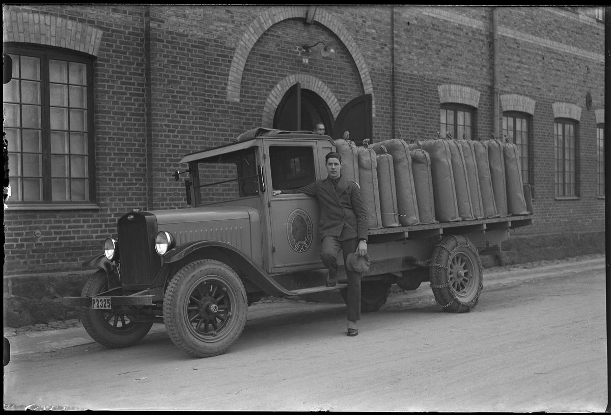 """En man står lutad mot en lastbil. På bilens dörr syns loggan för Alingsås Bomullsväveri och på flaket är textilbalar lastade. I fotografens egna anteckningar står det """"Siöstedt med bilen"""". Eventuellt är det Stig Svante Siöstedt."""