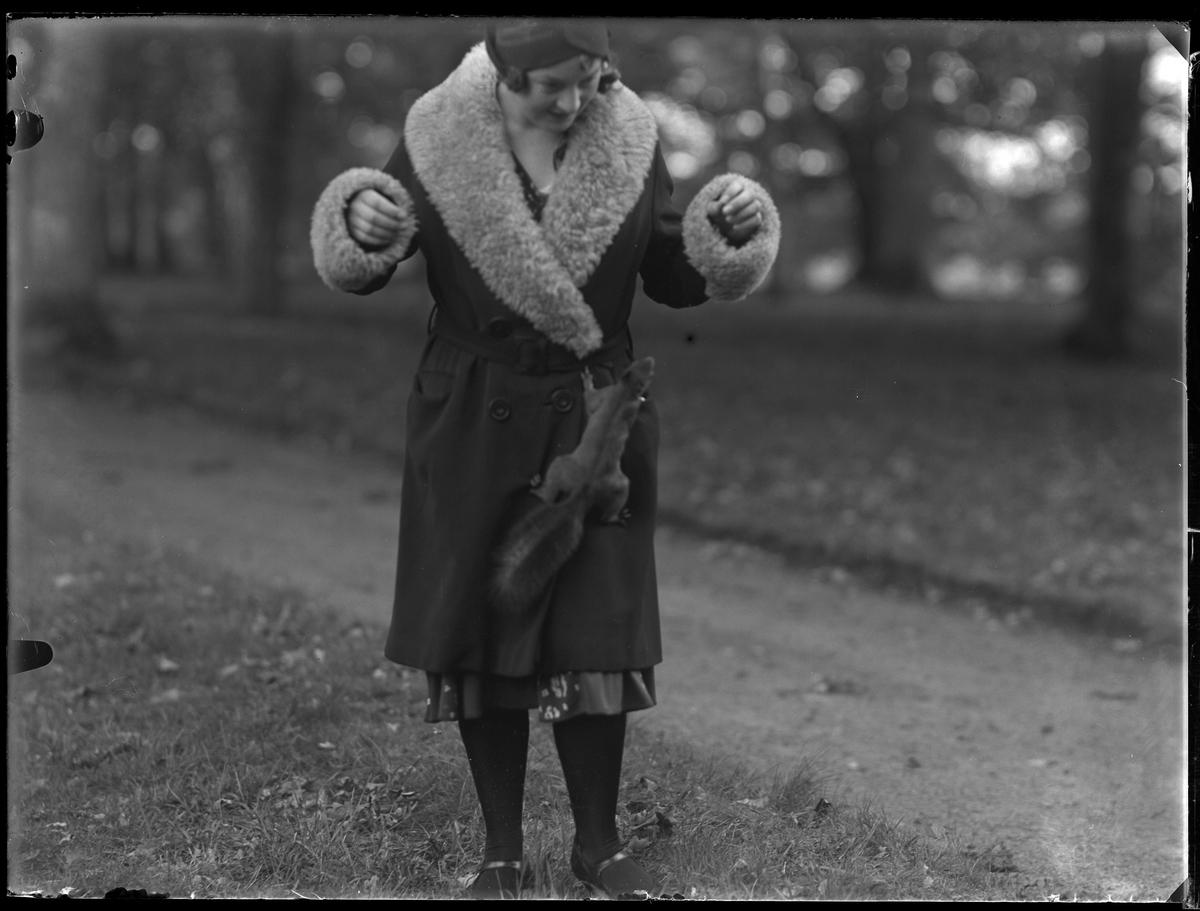 Gulli Svensson fotograferad i en park med en ekorre klättrandes upp för hennes pälskantade kappa.