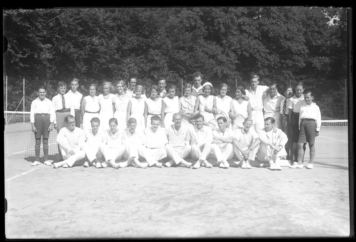 Gruppbild på medlemmar från Alingsås tennisklubb uppställda på en tennisplan.
