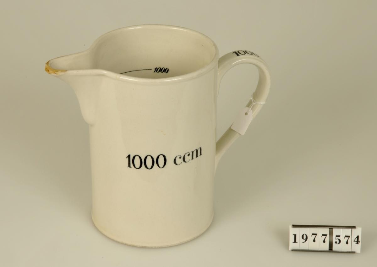 """Cylinderform. Utvändigt med text: """"1000 ccm"""",på handtaget """"1000"""" och invändigt med graderad måttskala.  Från Apoteket Hjorten, Alingsås."""