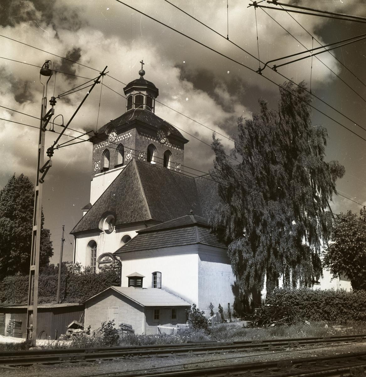 Bollnäs kyrka bakom ett järnvägsspår.