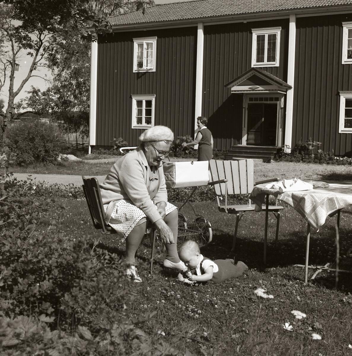 En kvinna sitter på en trädgårdsstol och passar ett litet barn som ligger på marken framför henne. I bakgrunden syns bostadshuset på gården Sunnanåker, 1970.