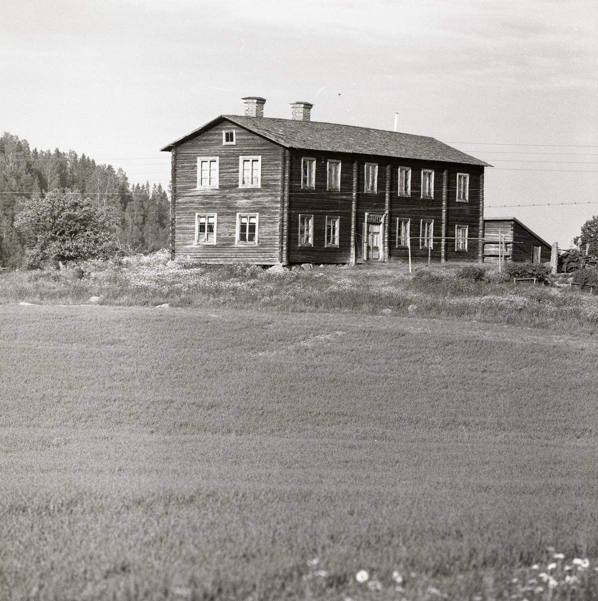 Ett bostadshus med många fönster placerat bakom en åker, 1967-68.