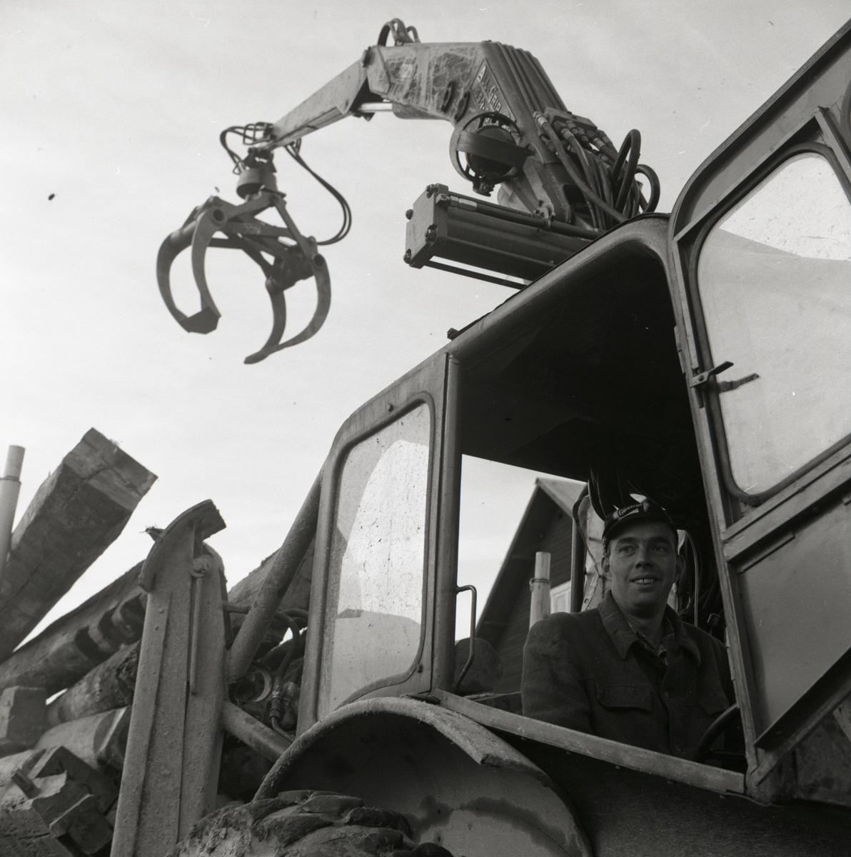 En man sitter i en traktor och har lastat vagnen full med timmerstockar i Rengsjö, 1967.