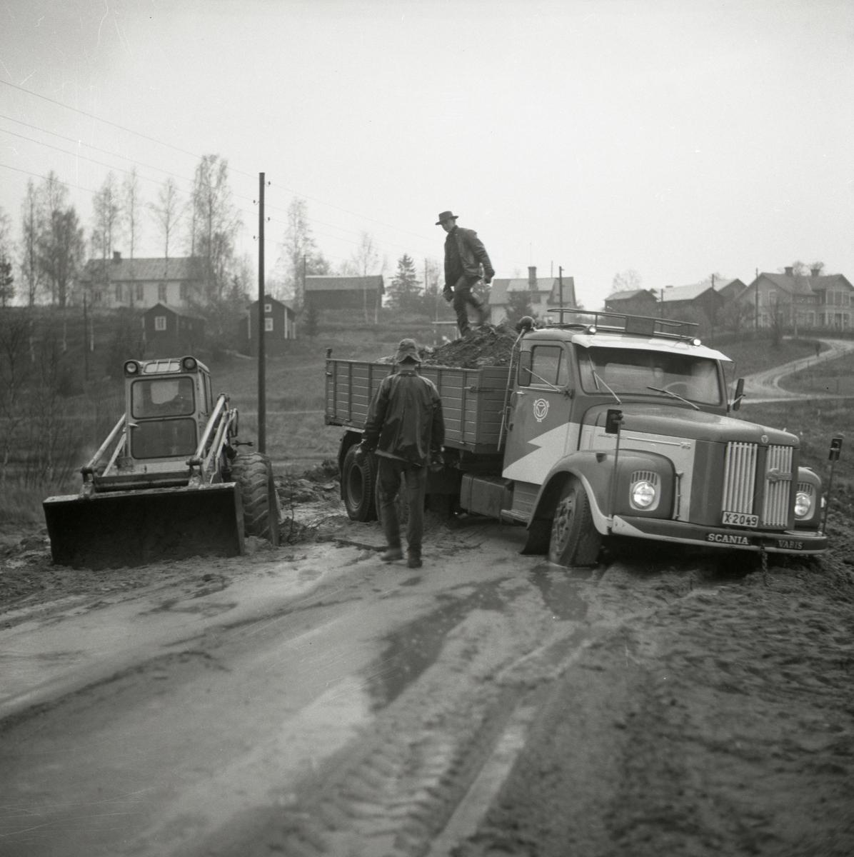 En lastbil har fastnat på en lerig väg och två män bedömer hur man ska få loss lastbilen. Intill vägen står en traktor.
