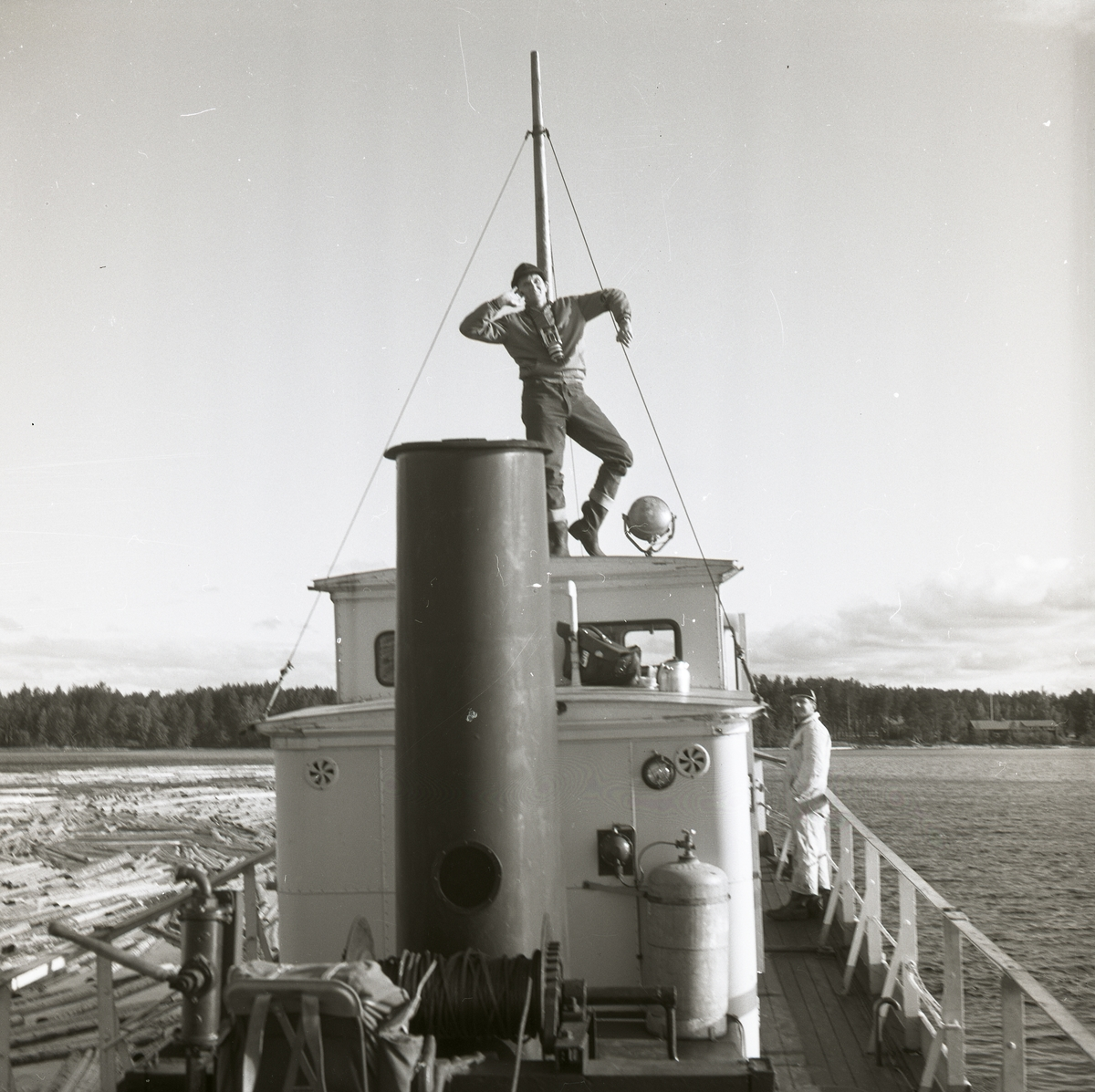En man står på taket på en av Dellenbåtarna och spexar. En annan man står lutad mot båtens reling. På vattnet syns timmer.