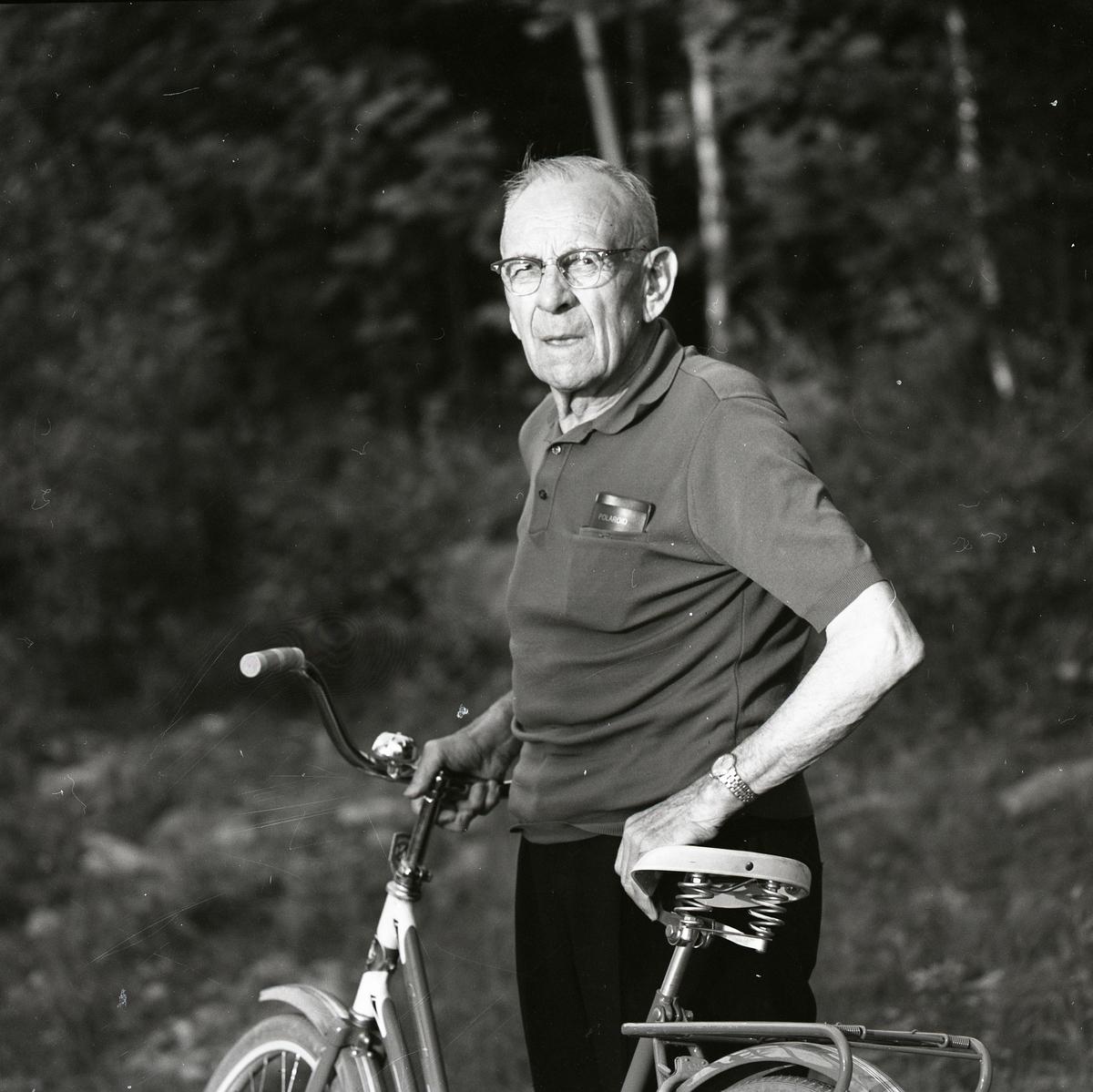 En äldre man i glasögon står med en cykel. I bröstfickan har han sitt glasögonfodral. En mild sol lyser på honom.