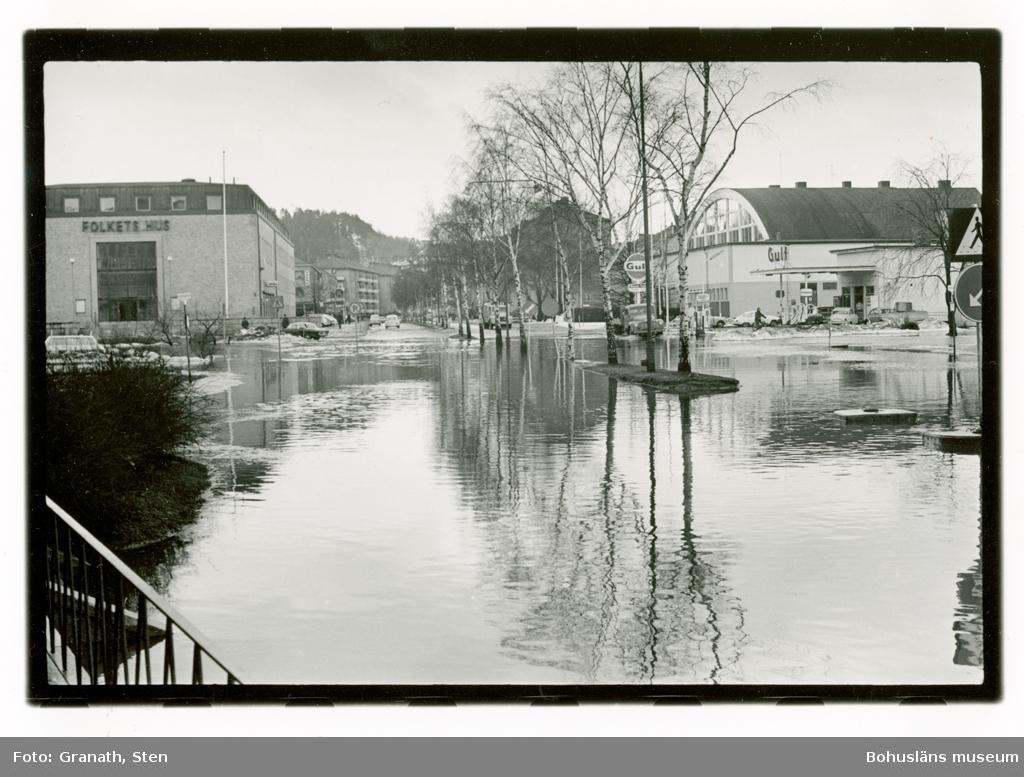 Översvämning på Göteborgsvägen, Uddevalla. I övre halvan av bilden syns Folkets Hus, en Gulf-mack och idrottshallen. Några bilar kör genom vattenmassorna. Det är snövallar längs vägarna och grenarna på träden i allén är kala. I nedre halvan av bilden syns vattenmassorna i vilka  omgivningarna och byggnaderna speglas.