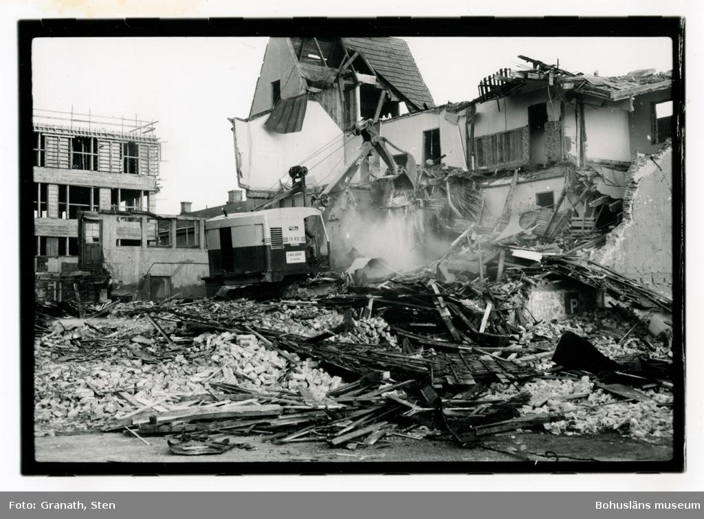 Rivning av stadshotellet på Kungsgatan. En grävmaskin i mitten av bilden river sönder ett flervåningshus. Till vänster står ett hus under uppförande där senare Nordbanken hade sitt kontor.
