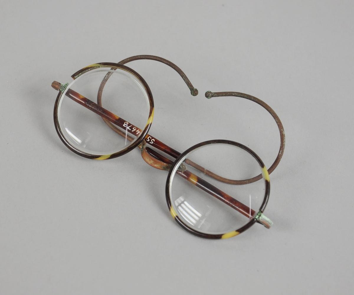 Runde briller med plastinnfarning og buede brillestenger. Innfatningen rundt det ene brilleglasset er knekt, og brilleglasset er derfor løst.