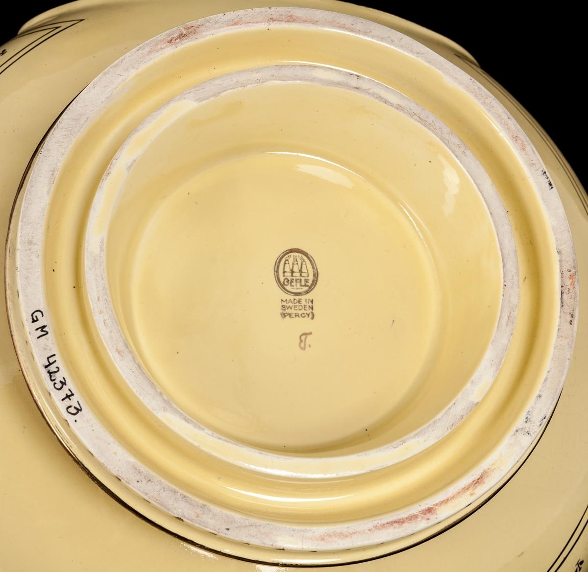 """Gul vinbål på fot med förgylld dekor. Två kurviga hänklar i sidorna. Lock med grepp i form av blomma. Förgylld empireinspirerad målad dekor. Påskrift framsida: """"Till Nils Sterner på fyrtioårsdagen från Gefle Porslinsfabriks aktiebolag."""" Under skriften syns porlsinsfabrikens tre ugnar.  På baksida: """"N S"""" i spegelmonogram  1899-1939 28/11  Stämplar under och i lock. I locket signerad Percy."""