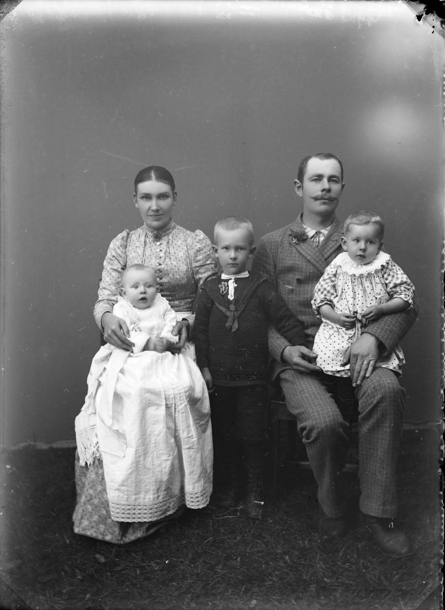 Familiebilde av 5 personer i atelier. Foreldre og 3 barn hvor muligens ett barn har dåpskjole.
