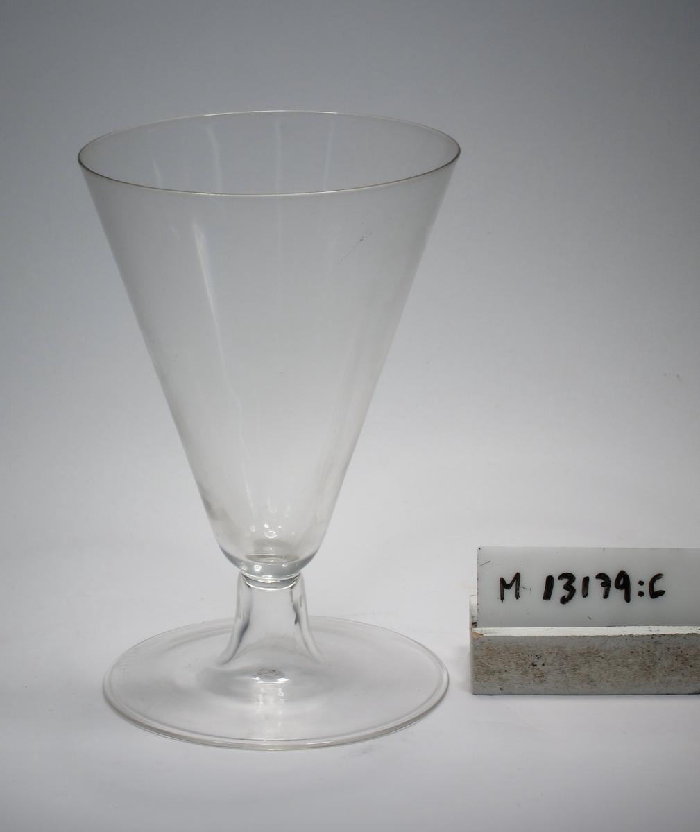 """Ölglas. Omvänt konformad kupa, kort ben. Den välvda foten går  direkt upp i det ihåliga benet. Ofärgat klarglas. Ovan angivna mått avser övre diameter. Fotdiameter: 87,5 mm. Bananformad, mörkblå etikett med text. Se """"Signering, märkning"""" ovan. Inskrivet i huvudkatalogen 1942. Funktion: Ölglas"""