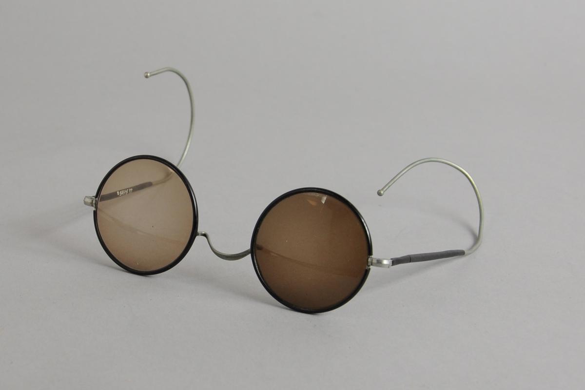 Runde mørke solbriller med metallinnfatning. Rundt brilleglassene og den innerste delen av stengene er forsterket med svart plast. Det høyre brilleglasset er mørkere enn det venstre.