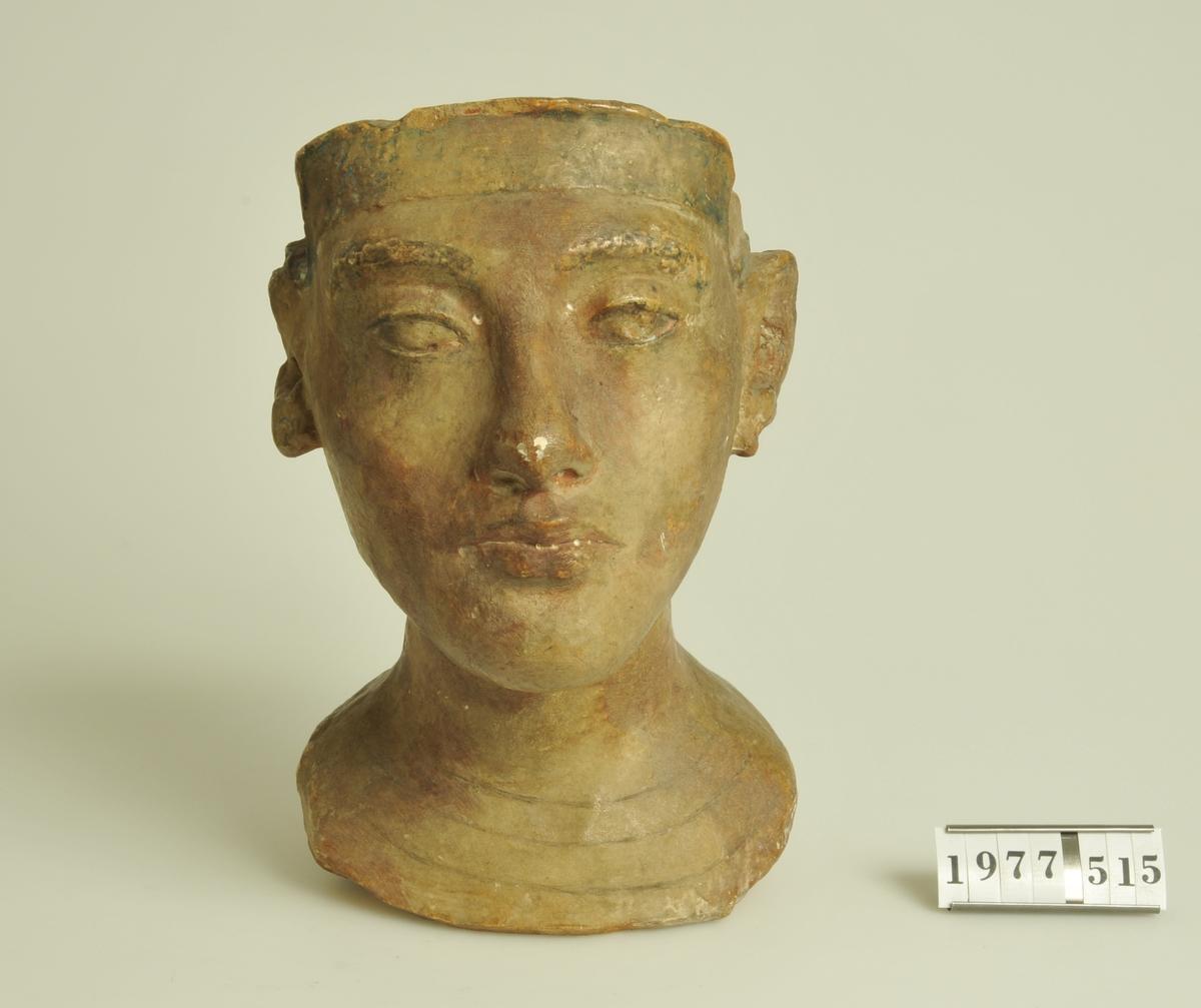 """Huvud av keramik med glasyr i rött och svart. Troligen kopia av egyptiskt gravfynd. Stämpel: I botten en mässingsplatta med text: """"FELIX NANNES MÃœNCHEN""""."""