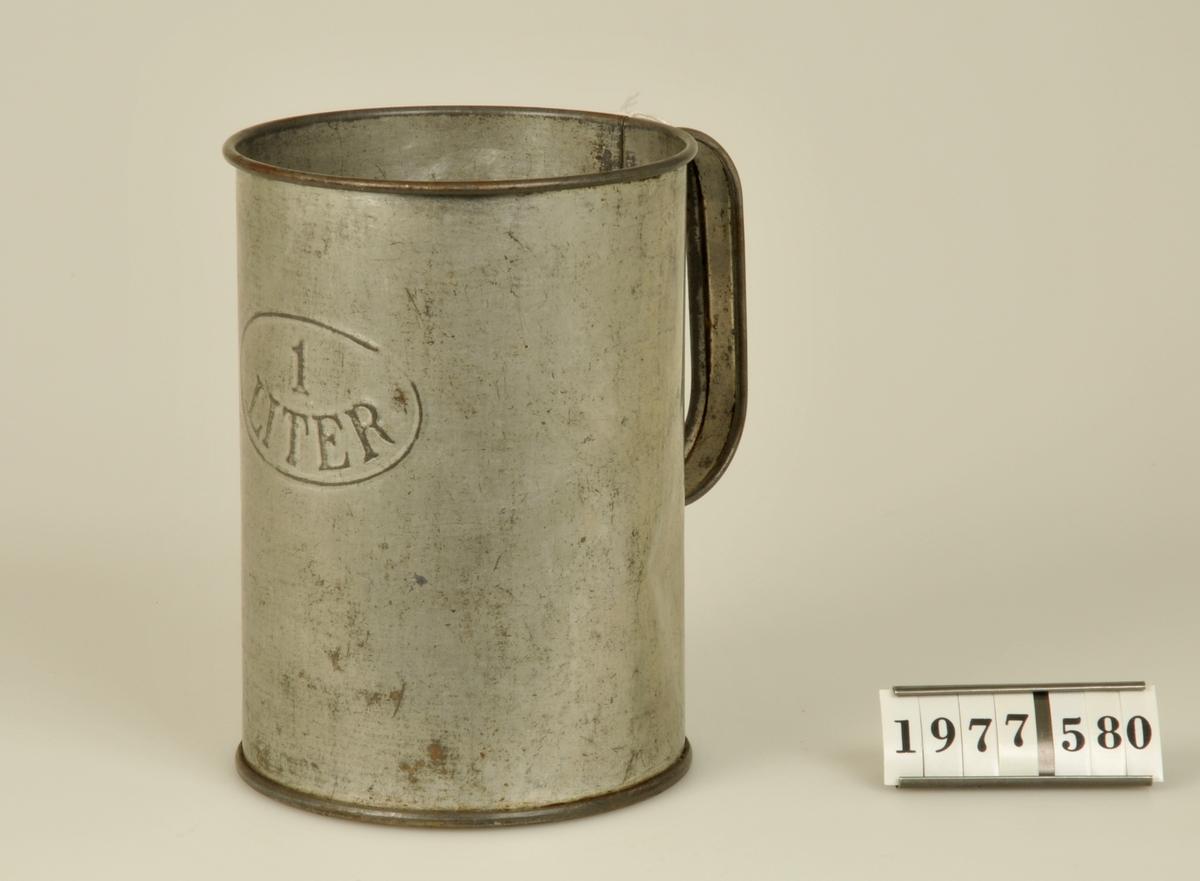 """Cylinderform. Med handtag. På framsidan texten: """" 1LITER"""" i relief inom en oval."""