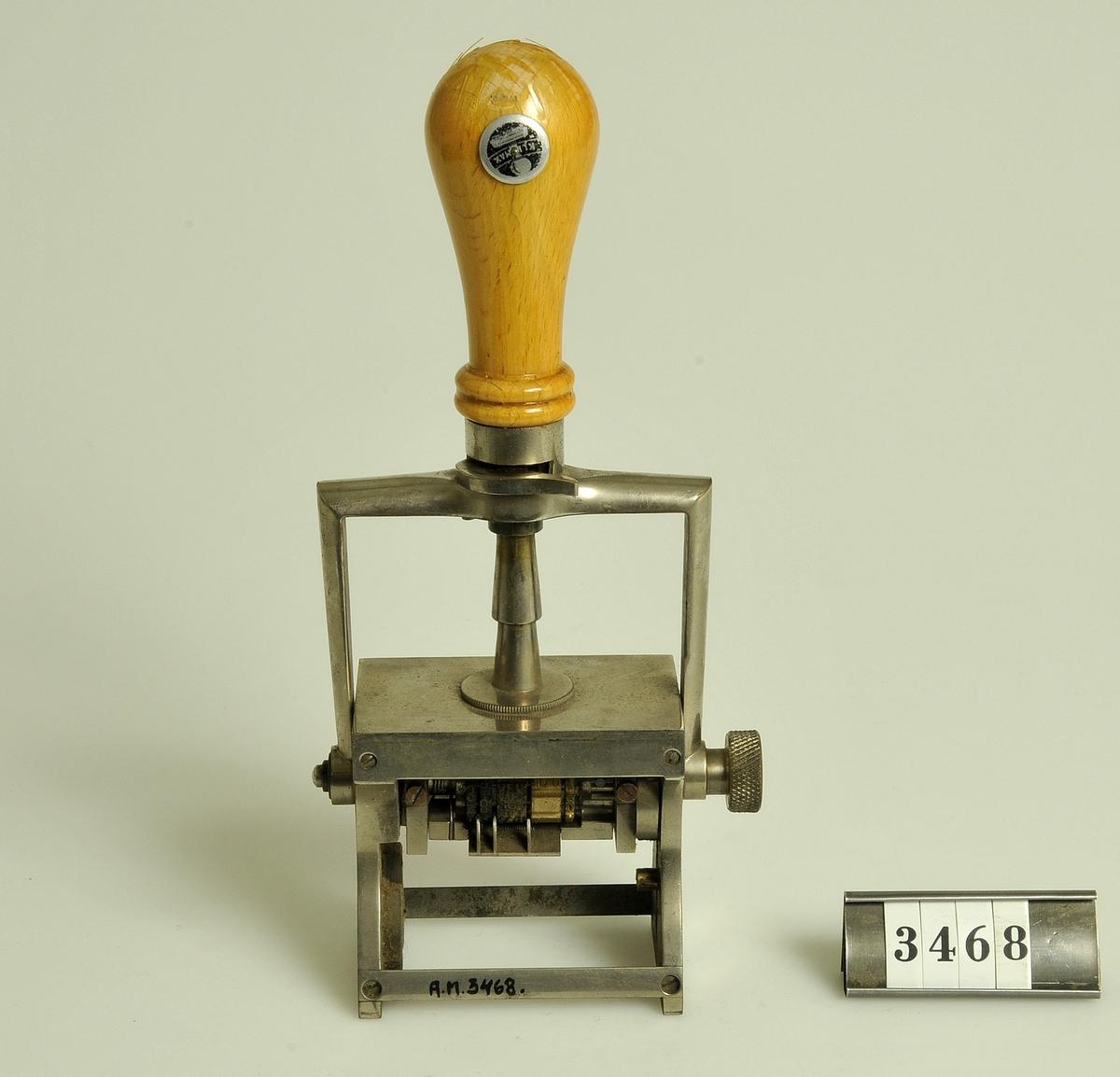 Datumstämpel. Tillverkad av metall med träskaft.