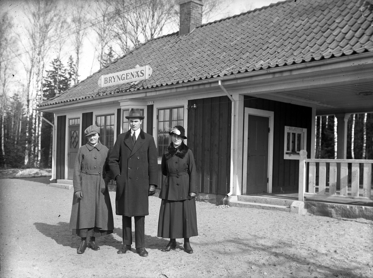 Två kvinnor och en man står framför Bryngenäs stationshus.   På andra sidan spåret låg ytterligare ett stationshus, Österbodarnes. De två godsen ville ha varsin stationsbyggnad. Ingen av byggnaderna står kvar idag, eventuellt är en av dem flyttad.