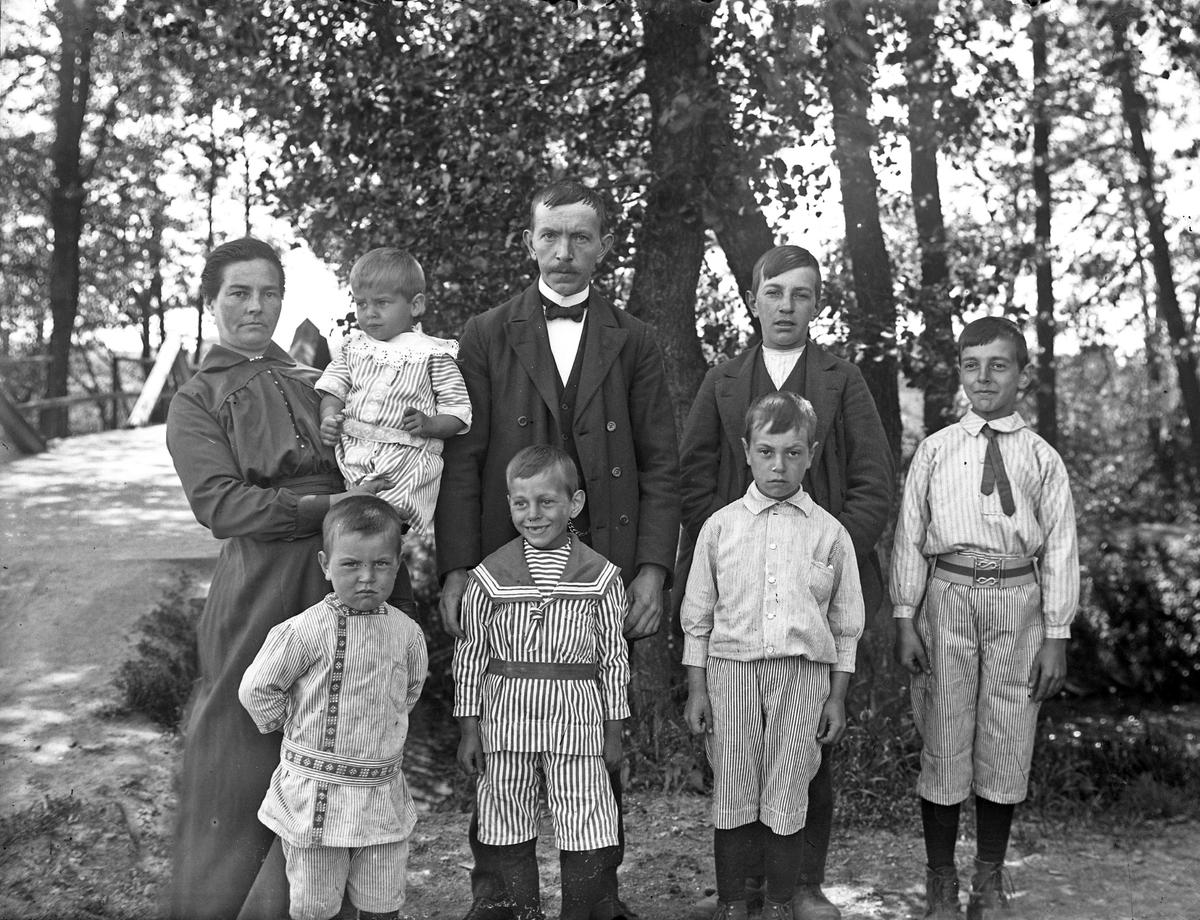 Familjen Holm, mor och far och sex söner fotograferade vid Nolby stock, den gamla bron över Säveån vid Alingsås landskyrkan. Familjen bodde i Alingsås, okänt var, fru Holm hade senare ostaffär i Alingsås.  Originalbild finns, bruntonat vykortspapper.