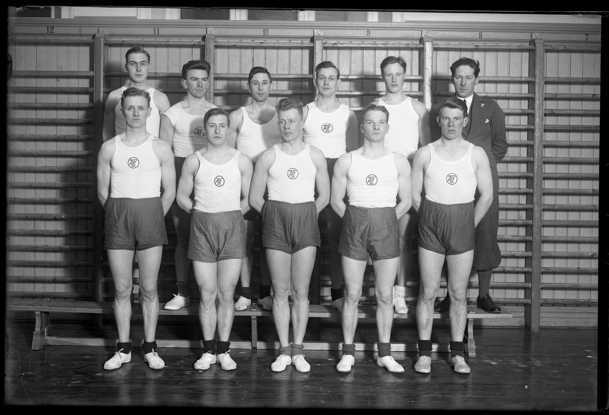 """10 män i gymnastikkläder (Alingsås Idrottsförening) står uppradade i två rader framför ribbstolar. Bredvid dem står en man i tweedkostym. I fotografens anteckningar står det """"Inomhusmästerskapet""""."""