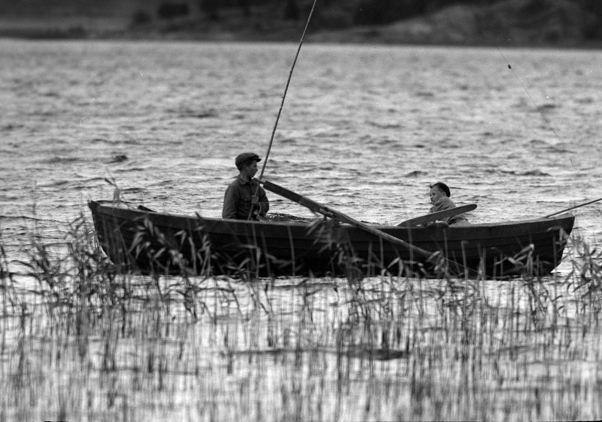 """Två pojkar sitter i en roddbåt. Den ena håller i ett metspö. I fotografens anteckningar står det """"35 films fr. semester på Halö""""."""