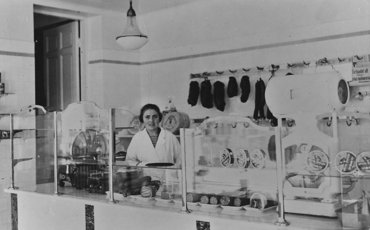 En kvinna står bakom en charkuteridisk i Skoglunds Charkuteri. Nygatan 13. Kvarteret Storken. Interör från butiken.
