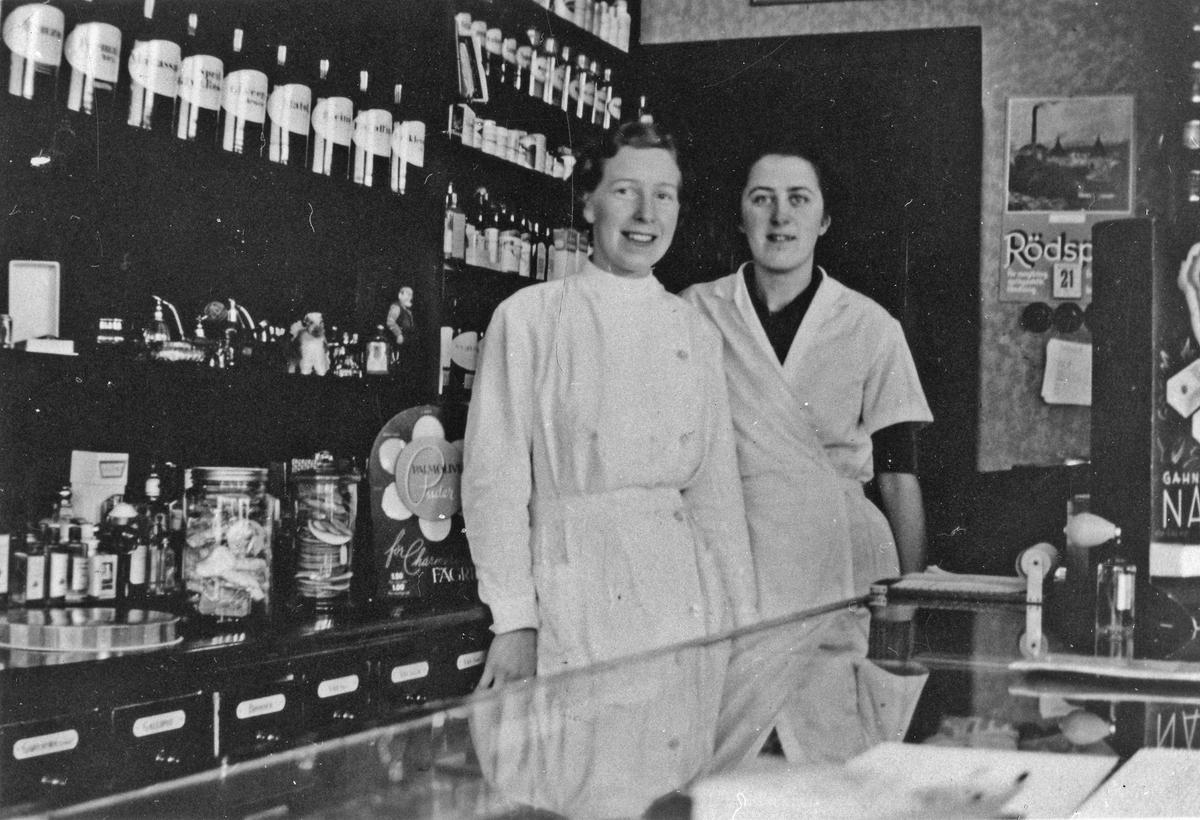 2 kvinnor, Kerstin Landgren och Elsa Landgren, i vita rockar står bakom en butiksdisk och tittar in i kameran. Bakom sig har dom en hylla fylld med glasburkar. Landgrens Kemigrafiska Affär. Kungsgatan 41.