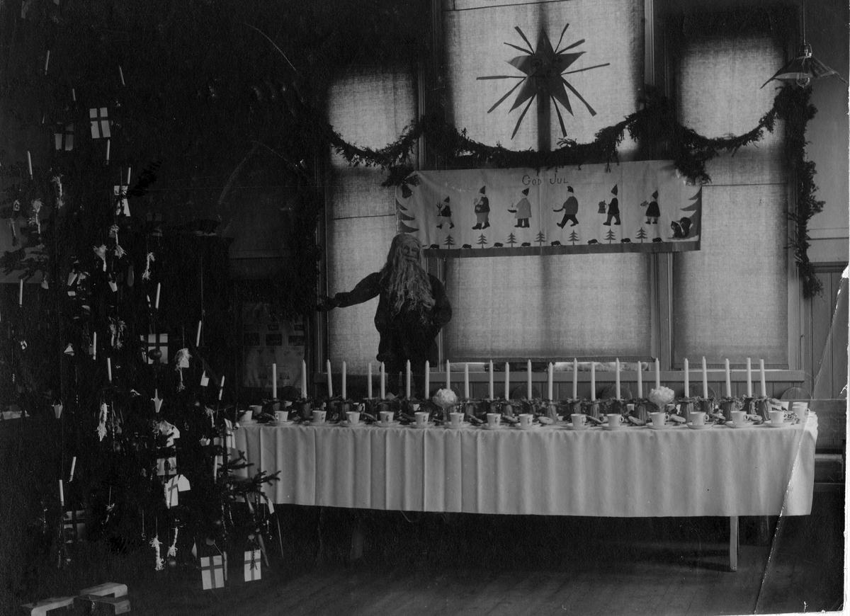 """Bilden visar ett uppdukat långbord med kaffeporslin och ljusstakar. Bakom bordet en dekorativ jultomte, väggbonad med texten """"GOD JUL"""" och en stor julstjärna. Till vänster ses en utsmyckad julgran med flaggor och ljus. """"Syföreningens"""" fest för barn """"från mindre bemedlade föräldrahem"""". I början av 1900-talet."""