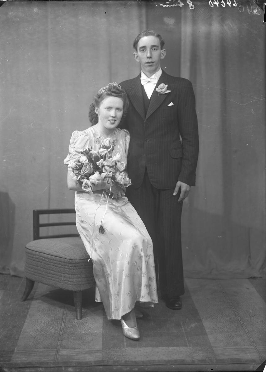Portrett. Brudebilde. Ung kvinne  i lys kjole med tiarra på hodet og blomsterbukett i fanget og ung mann i mørk dress med lys sløyfe. Brudepar. Bestilt av Johs. Johannessen. Rossebø.