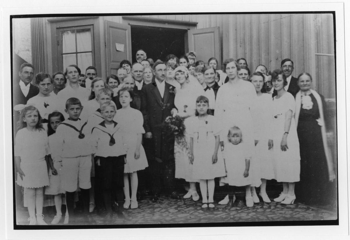 Ett fyrtiotal bröllopsgäster inklusive brudparet i en gruppbild. De står på gården utanför ett hus. Originalet i vykortsformat, bruntonat.