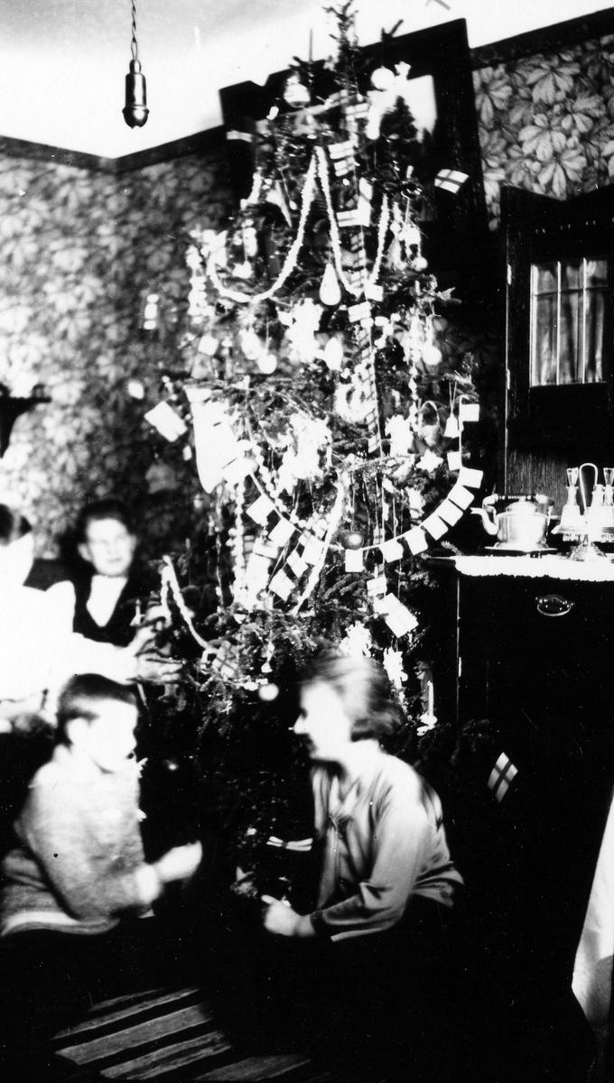 Några barn sitter vid en gran som är kraftigt pyntad, på en hylla till höger står en servis.