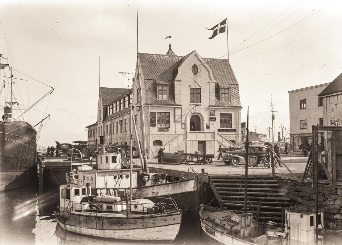 Dampskipskaia i Harstad med ekspedisjonsbygningen og fartøyer i forgrunnen.
