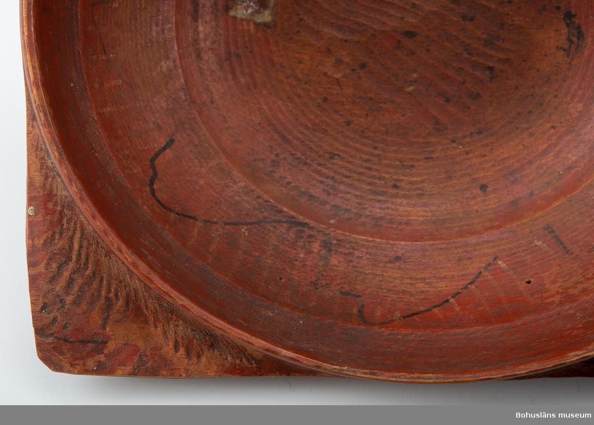 """Svarvad låg skål med fyra utskjutande """"snibbar"""" nedanför den runda mynningen. De sitter placerade i en fyrkant. Målad i rostrött på både ut- och insida. På """"snibbarna"""" samt inuti löper det en svart vågig dekorlinje. Inuti finns det även spår av  guldränder. Färgen är sliten. Skadedjursangrepp. I botten har det suttit en äldre 'frimärksetikett'. Under botten  är """"NBS"""" inskuret.  Se Knut Adrian Anderssons """"Katalog I, A. yngre föremål"""" under Uddevalla museum/förening D 2A:1 i arkivet.  Förvärvad från Samuelsson, Svante Justivius; Gästgivare, Sörbo, Orust.  Litt;  Hallset, G.: Svarvning i Ås härad, s. 25-32 och Svenningson, S.: Streckmålade toarpsaskar, s. 33-44, i Från Borås och de sju häraderna, Fässingen, 2001 - Årgång 47. Kjellberg, Sven T, Ölets käril - Om bollar med handtag kallskålar och snibbskålar, Kulturen 1964, Lund 1964, s. 49-59. Se bilagepärm: Kopia av tidningsartikel """"Flitigt svarvande i Sjuhärad"""" av Gunilla Hallset i Borås Tidning lördagen den 19 maj 2001.  Ur handskrivna katalogen 1957-1958: Snipaskål L.22. Br. 20,5. Trä. Rödmålad. 4 hörn. Märkt: N.B.S. Föremålet helt. Hede. Bohusl.  Lappkatalog: 67"""