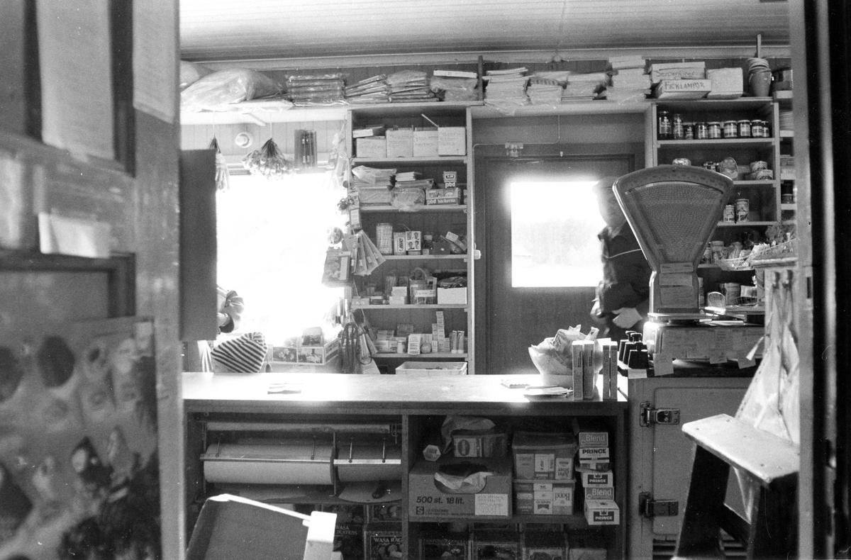 Bilden är tagen inifrån Doris Kiosk och Specerier, bakom disken, mot huvudingången. Vid dörren ses en man och till vänster precis vid disken ses ett litet barn med randig mössa.
